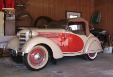 1938 American Bantam roadster with early removable fender skirts, hood ornament, wheel trim rings and convertible top.